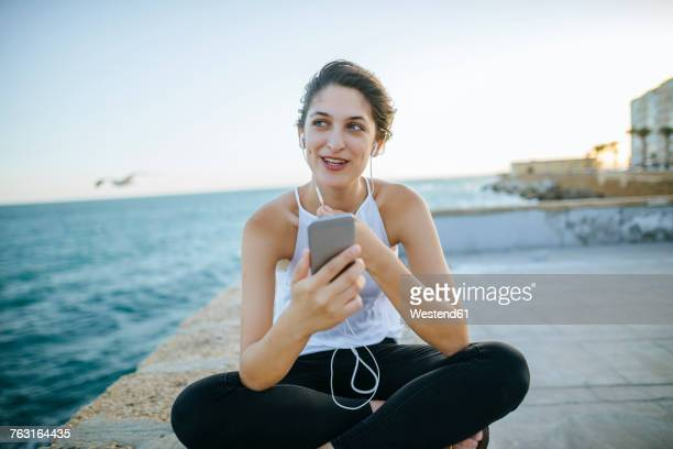 Young woman talking with hands-free phone on boardwalk
