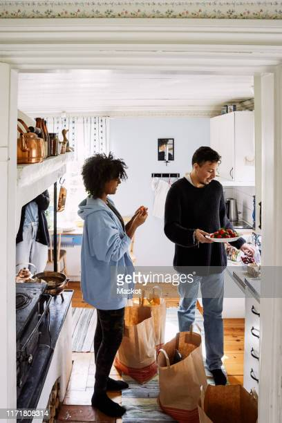 young woman talking with male friend holding strawberries in plate while standing at home seen through doorway - cottage stock pictures, royalty-free photos & images