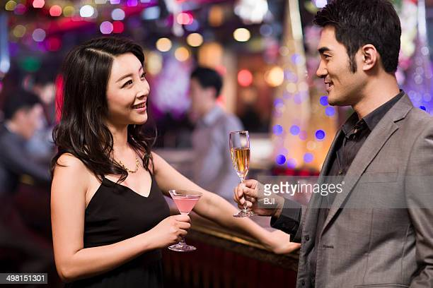 Young woman talking with young man in bar