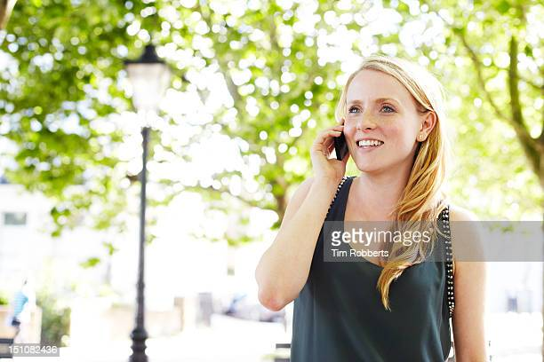 young woman talks on smart phone, green urban area - sleeveless top stock pictures, royalty-free photos & images