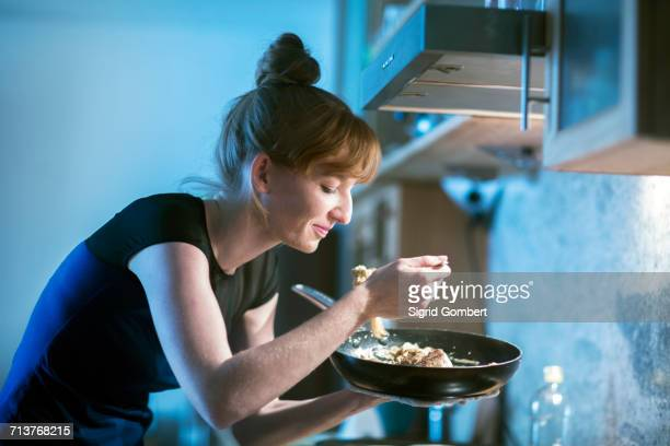 young woman tasting food from frying pan - sigrid gombert stock-fotos und bilder