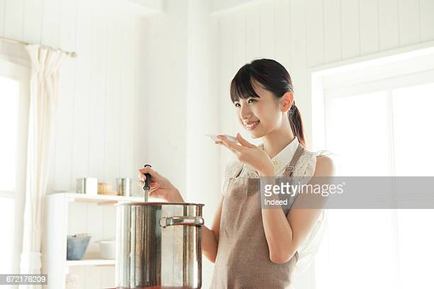 Young woman tasting soup at kitchen