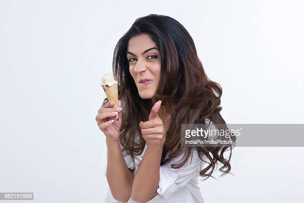 Young woman teasing while holding ice cream cone over white background