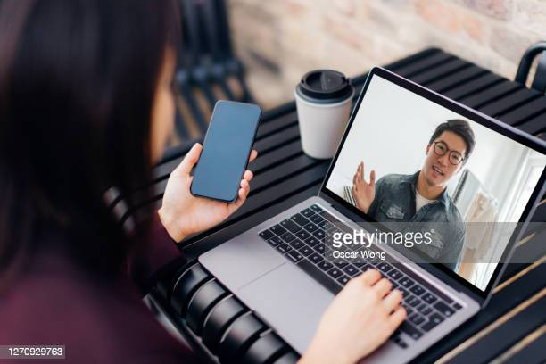 young woman teleconferencing with laptop at cafe - adult stock pictures, royalty-free photos & images