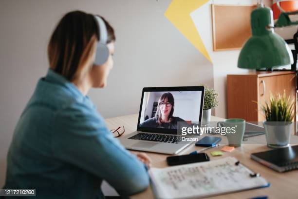 young woman teleconferencing with sister on laptop on conference call - videoconferenza foto e immagini stock