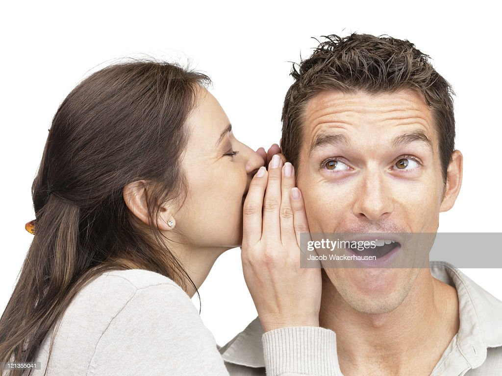 Young woman telling secret to a man : Stock Photo