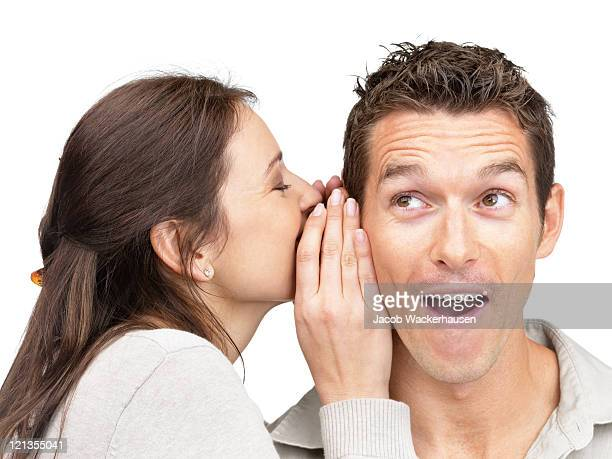 Young woman telling secret to a man