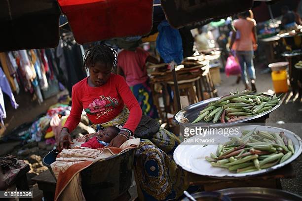 A young woman tends a baby in a market area on November 19 2015 in Conakry Guinea Guinea is currently counting down the necessary 42 days period...