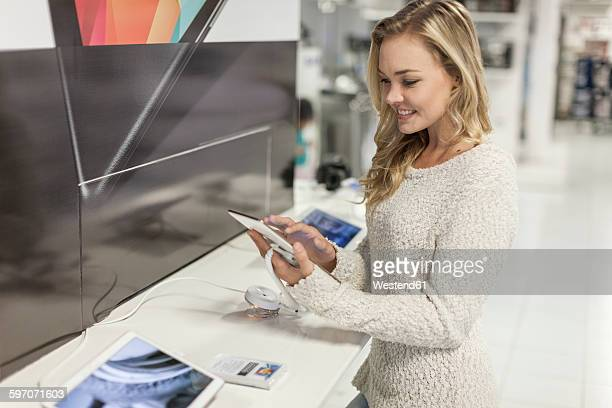 Young woman testing digital tablet in a shop