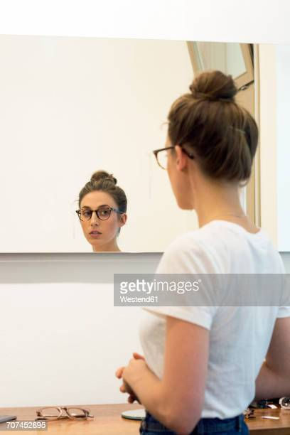 young woman testing glasses frames in an optician shop - woman in mirror stock photos and pictures