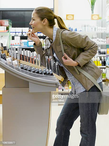 young woman testing lipstick in perfume store