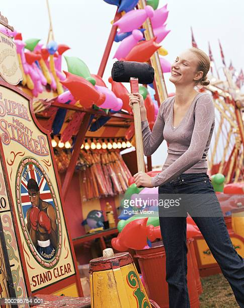 Young woman testing strength at fairground, smiling