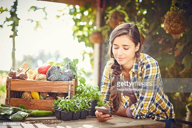 Young woman text messaging at organic farm