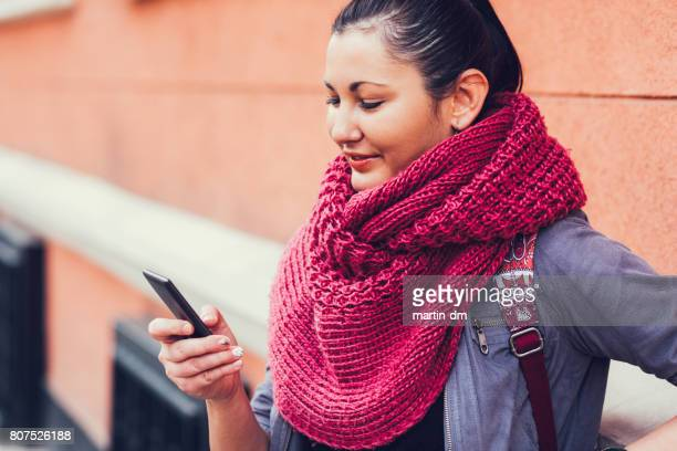 Young woman text messaging at the street