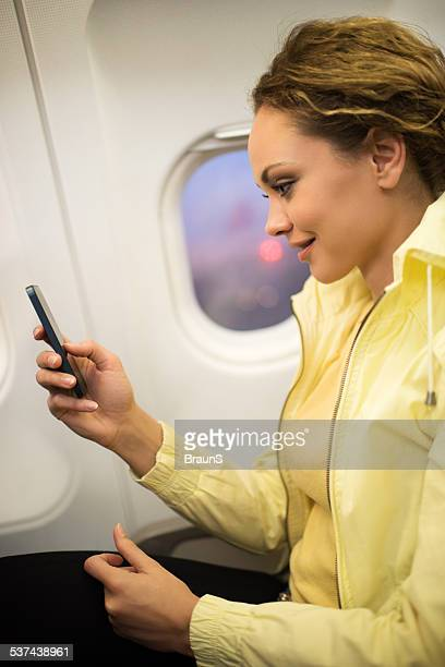 Young woman text messaging in airplane.