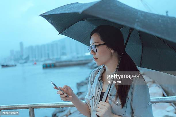 Young woman text messaging in rainy city street