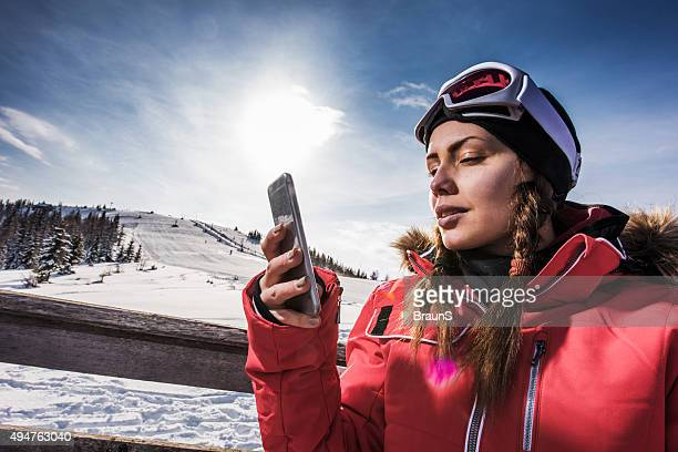 Young woman text messaging on mobile phone at ski resort.