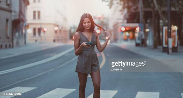 young woman text messaging on pedestrian crossing - zebra crossing stock pictures, royalty-free photos & images