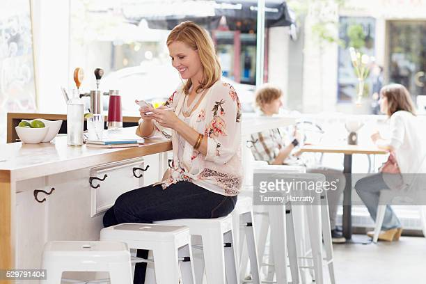 young woman texting at bar counter - tammy bar stock pictures, royalty-free photos & images
