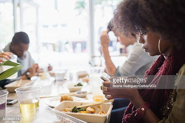 Young woman texting at table in restaurant
