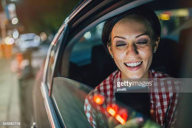 Young woman texting in a car at night