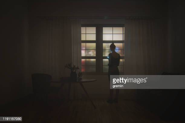 young woman texting in the living room at night - dark stock pictures, royalty-free photos & images