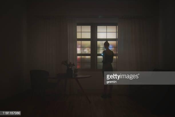 夜のリビングルームでテキストメッセージを送る若い女性 - 依存症 ストックフォトと画像