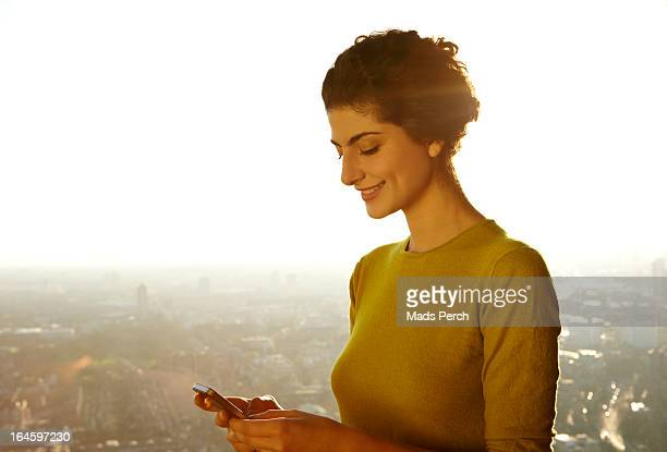 Young woman texting on her smartphone with city vi