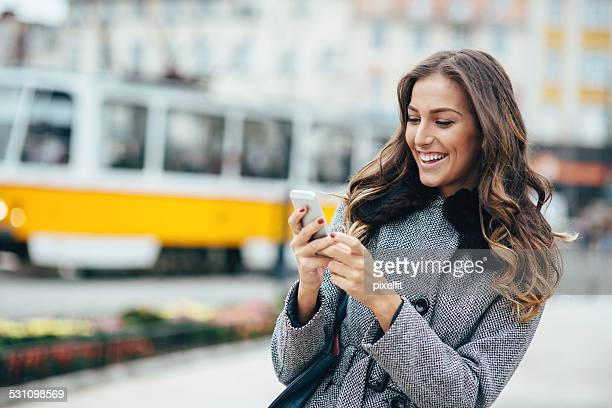 Young woman texting on smart phone outdoors