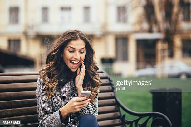 young woman texting on smart phone outdoors - surprise stock pictures, royalty-free photos & images