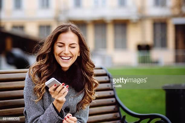 Jeune femme à envoyer des SMS sur le téléphone intelligent en plein air