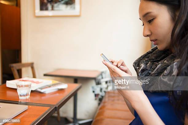 Young woman texting on smartphone in cafe