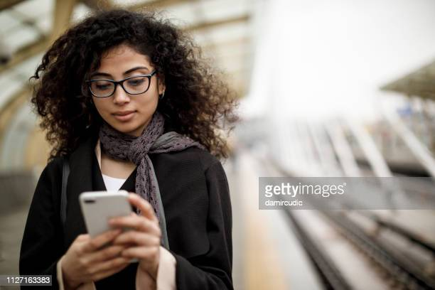 jonge vrouw sms op de telefoon - wachten stockfoto's en -beelden