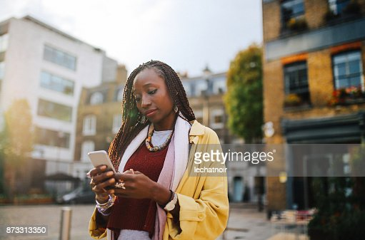 Young woman texting on the street in Shoreditch, London