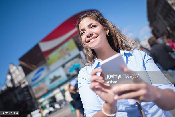 Young woman texting on the street