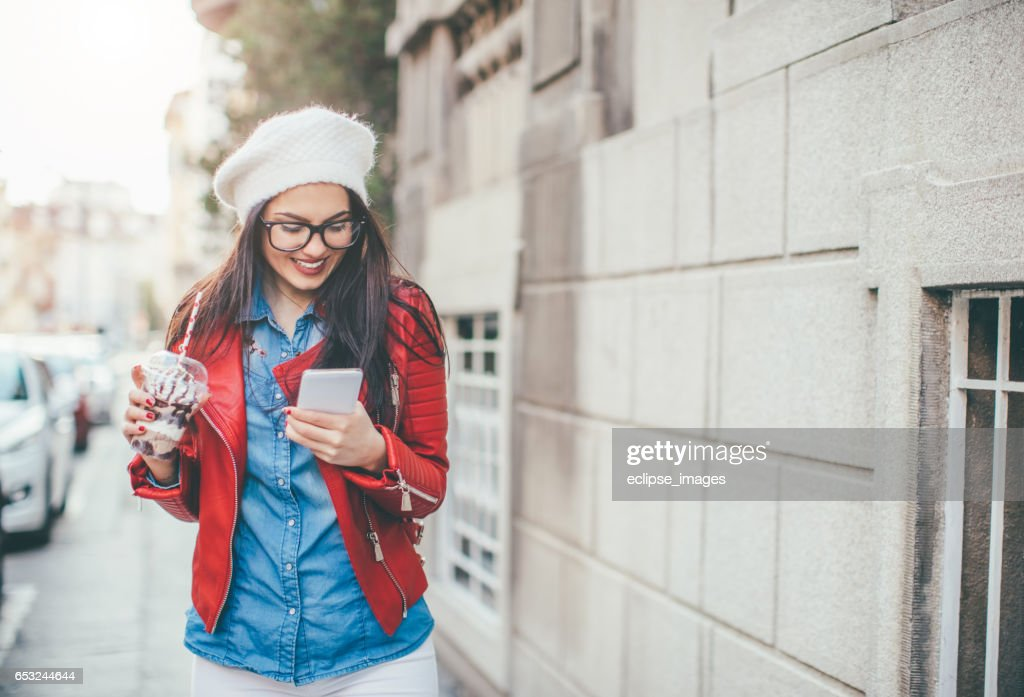 Young woman texting outdoors : Stock Photo