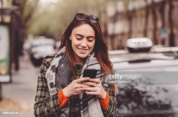Young woman texting outside