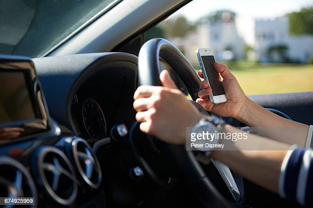 young woman texting while driving - woman texting stockfoto's en -beelden