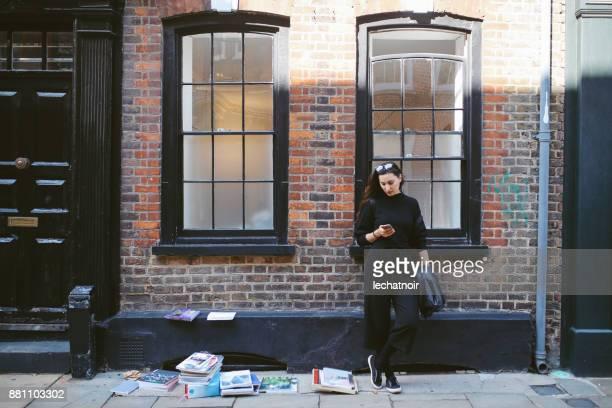 jonge vrouw texting tijdens het wachten op de straten van londen, east end - londen stadgebied stockfoto's en -beelden