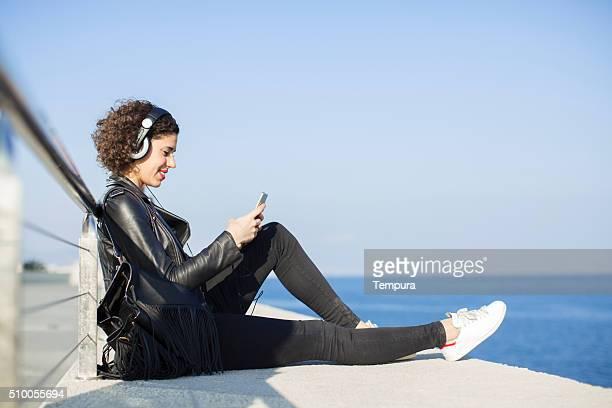 mujer joven sms con su teléfono inteligente y escuchar música. - radio hardware audio fotografías e imágenes de stock