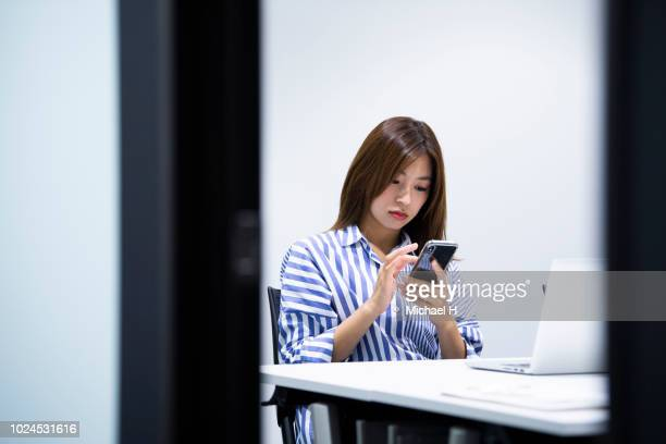 young woman texting with smart phone at laptop in office - 可動性 ストックフォトと画像