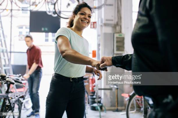 young woman thanking mechanic for repairing bike - fist bump stock pictures, royalty-free photos & images