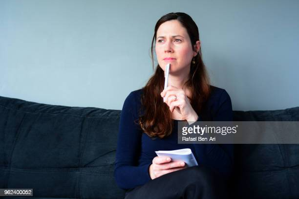 young woman thinking about to do list at home - rafael ben ari stock pictures, royalty-free photos & images