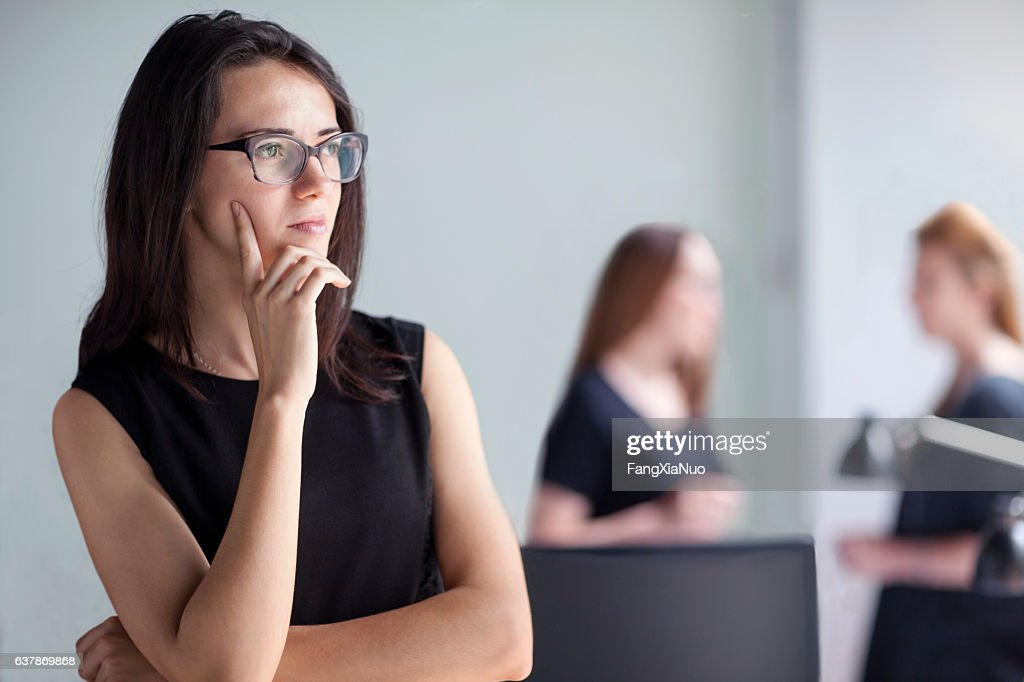 Young woman thinking in business office : Stock Photo