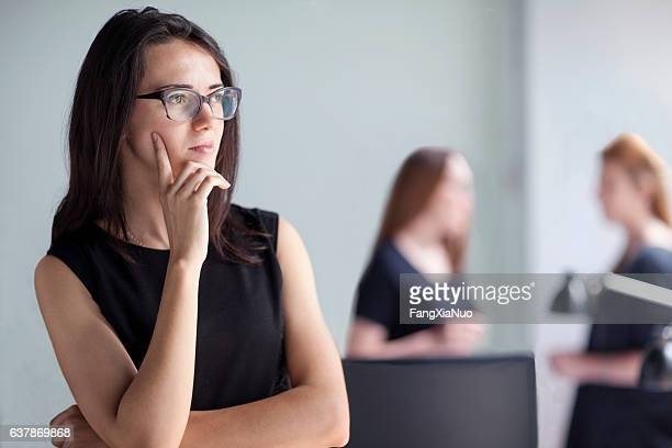 young woman thinking in business office - beslissingen stockfoto's en -beelden