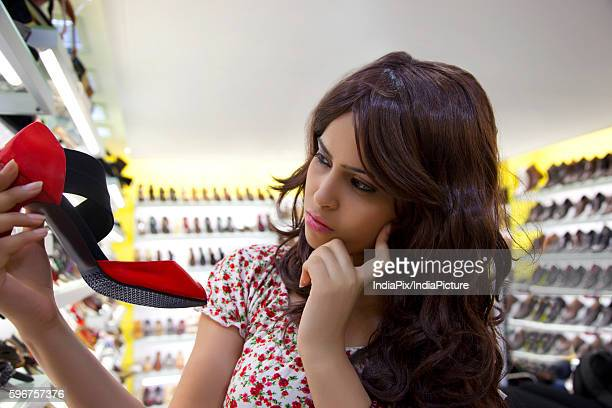 Young woman thinking while looking at sandal