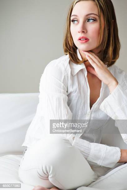 Young woman thinking while sitting on sofa