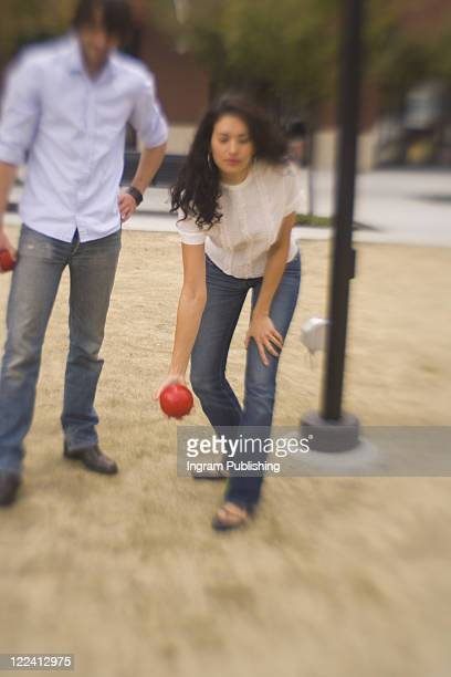 young woman throwing a ball with a young man standing beside her - jean ingram stock pictures, royalty-free photos & images