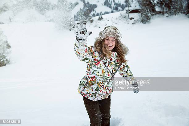 young woman throwing a snowball - ski wear stock pictures, royalty-free photos & images
