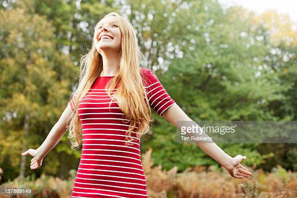 Young woman throwing arms back.